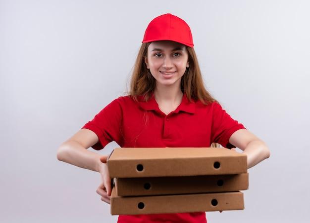 Glimlachend jong leveringsmeisje in rood uniform die pakketten op geïsoleerde witte muur uitrekken