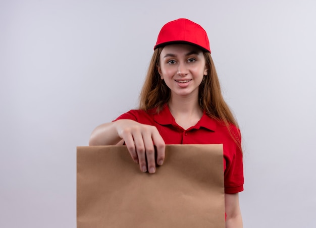 Glimlachend jong leveringsmeisje in rood uniform die zich uit papieren zak op geïsoleerde witte muur uitstrekt