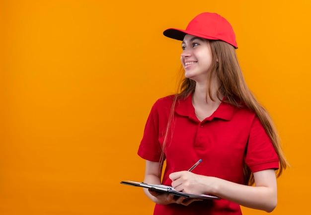 Glimlachend jong leveringsmeisje in rood uniform holdingsklembord en pen die naar linkerkant op geïsoleerde oranje ruimte met exemplaarruimte kijken