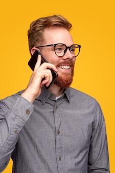 Glimlachend jong mannetje in grijs overhemd en glazen die gesprek op smartphone hebben die weg op gele achtergrond kijken