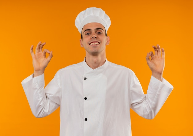 Glimlachend jong mannetje koel dragen uniforme chef-kok met okey gebaren