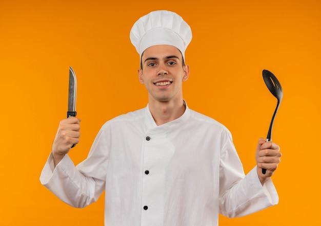 Glimlachend jong mannetje koel dragend mes en pollepel van de chef-kok eenvormig bedrijf