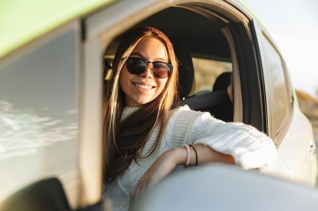 Glimlachend jong meisje autorijden tijdens zonsondergang, kijkend naar het raam