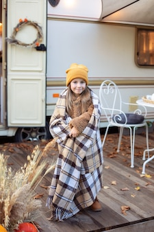Glimlachend jong meisje bedekt met deken staande op veranda rv huis om op te warmen in herfsttuin