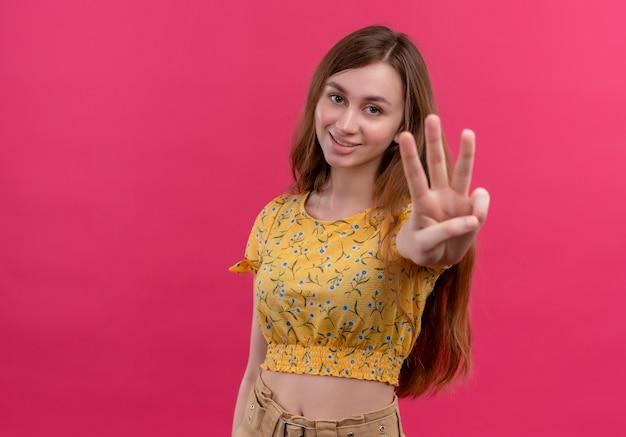 Glimlachend jong meisje dat drie op geïsoleerde roze muur met exemplaarruimte toont