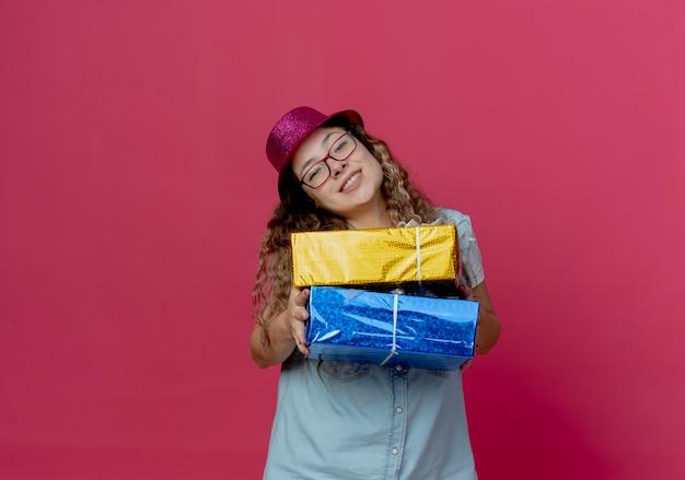 Glimlachend jong meisje dat een bril en een roze hoed draagt die giftdozen standhoudt bij camera die op roze wordt geïsoleerd