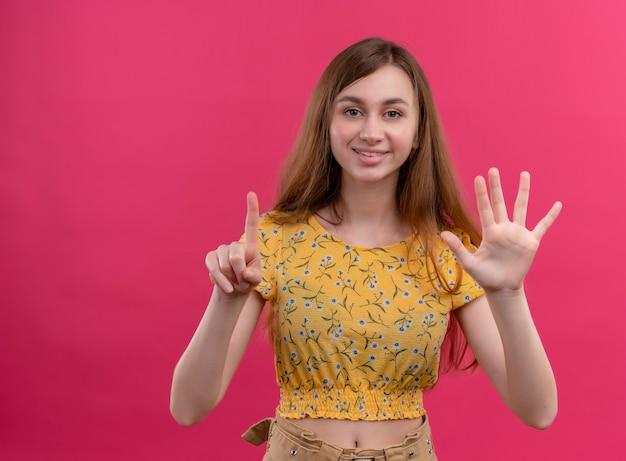 Glimlachend jong meisje dat één en vijf op geïsoleerde roze muur met exemplaarruimte toont