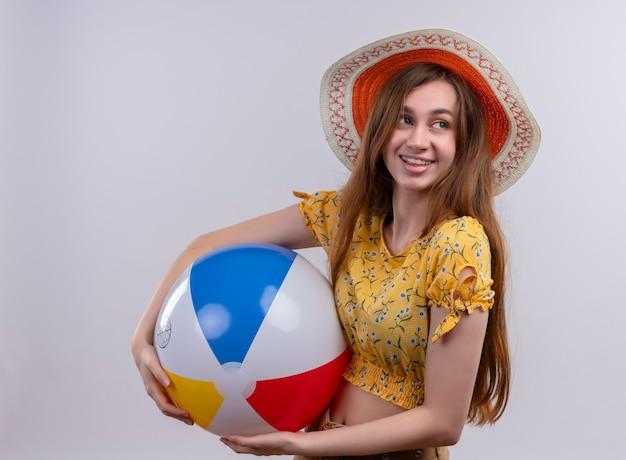 Glimlachend jong meisje dat het strandbal van de hoedholding draagt die rechterkant op geïsoleerde witte muur bekijkt