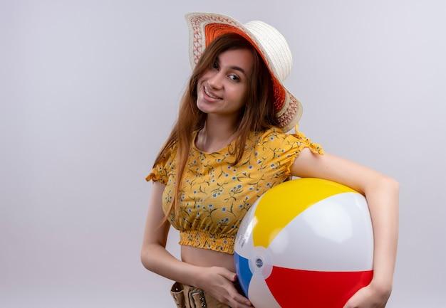Glimlachend jong meisje dat het strandbal van de hoedholding op geïsoleerde witte muur met exemplaarruimte draagt