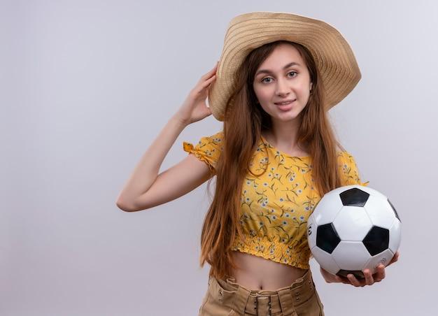 Glimlachend jong meisje dat het voetbalbal van de hoedholding draagt die hand op hoed op geïsoleerde witte muur met exemplaarruimte zet