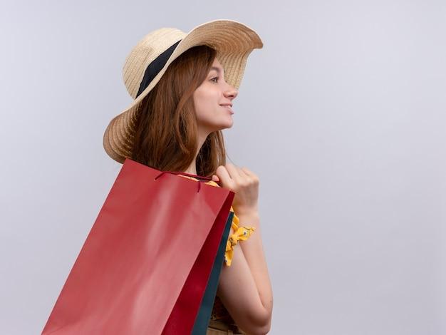 Glimlachend jong meisje dat hoed draagt die papieren zakken houdt die zich in profiel bekijken op geïsoleerde witte muur met exemplaarruimte