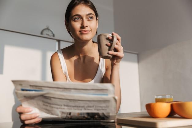 Glimlachend jong meisje dat in de ochtend bij de keuken staat, krant leest, thee drinkt