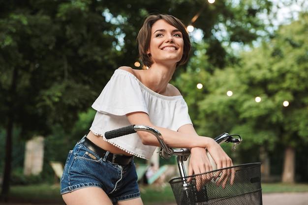 Glimlachend jong meisje dat in de zomerkleren op een fiets zit