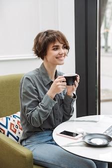 Glimlachend jong meisje dat koffie drinkt terwijl ze binnenshuis aan de cafétafel zit