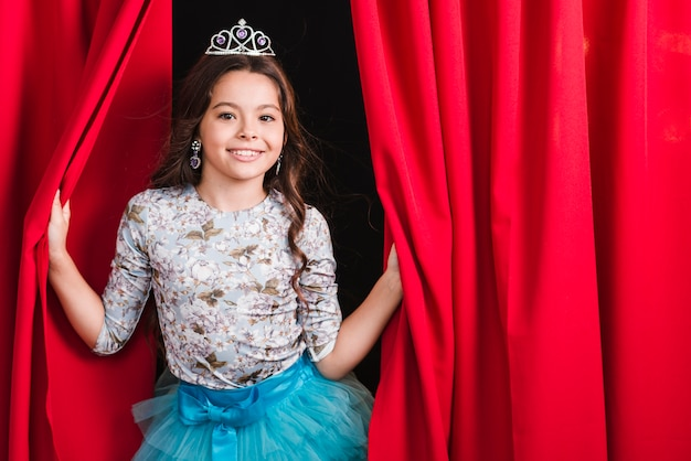 Glimlachend jong meisje dat kroon draagt die uit van rood gordijn kijkt