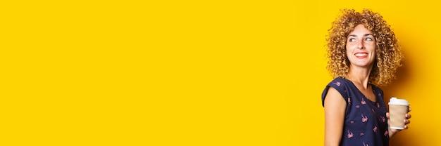 Glimlachend jong meisje dat met krullend haar document kop op gele oppervlakte houdt