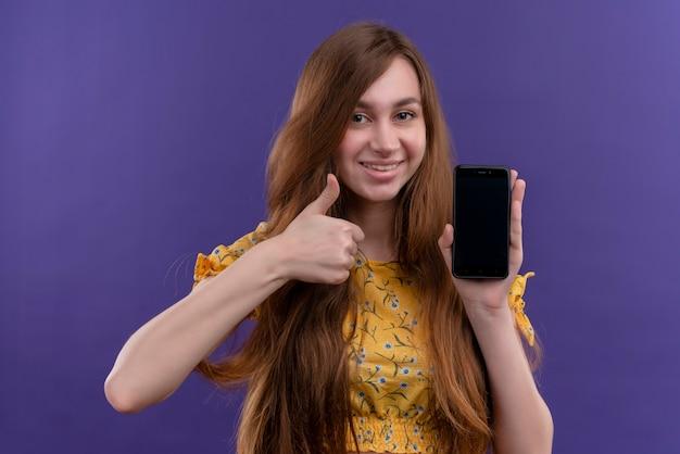 Glimlachend jong meisje dat mobiele telefoon houdt en duim op geïsoleerde purpere muur toont