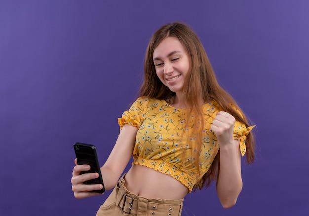 Glimlachend jong meisje dat mobiele telefoon houdt en vuist op geïsoleerde purpere muur opheft