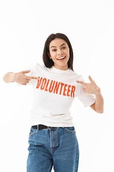 Glimlachend jong meisje dat vrijwilligerst-shirt draagt dat geïsoleerd over een witte muur staat, wijzend