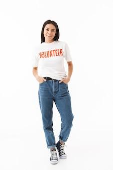 Glimlachend jong meisje dat vrijwilligerst-shirt draagt dat zich geïsoleerd over witte muur bevindt