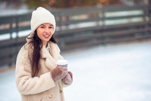 Glimlachend jong meisje die op ijsbaan in openlucht schaatsen
