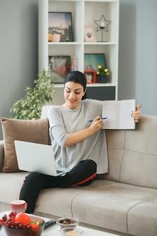 Glimlachend jong meisje gebruikte laptop vasthouden en wijst naar boek met pen zittend op de bank in de woonkamer