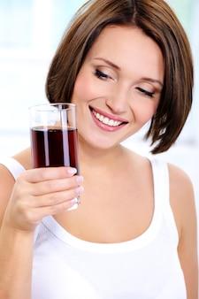 Glimlachend jong meisje houdt een glas granaatappelsap