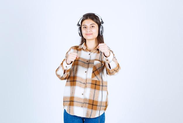 Glimlachend jong meisje in koptelefoon luisteren naar lied en staan.