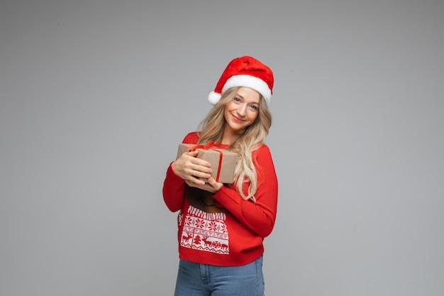 Glimlachend jong meisje in rode kerstmuts en warme wintertrui met cadeau poseren op grijze studio achtergrond met kopieerruimte