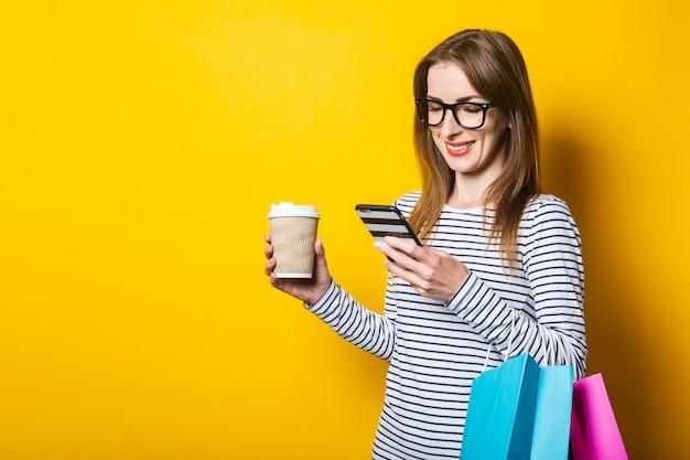 Glimlachend jong meisje kijkend naar de telefoon, met een papieren kopje koffie en met boodschappentassen op een gele achtergrond