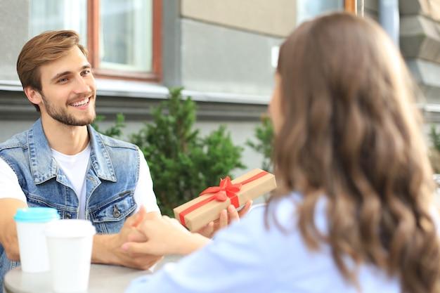 Glimlachend jong meisje met een date met haar vriendje in de coffeeshop, man met huidige doos.