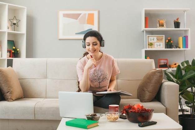 Glimlachend jong meisje met een koptelefoon met een notitieboekje gebruikte laptop zittend op de bank achter de salontafel in de woonkamer