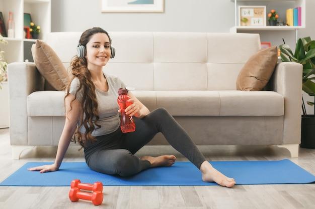 Glimlachend jong meisje met een koptelefoon met een waterfles voor de bank in de woonkamer