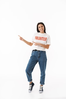 Glimlachend jong meisje met een vrijwilligerst-shirt dat geïsoleerd over een witte muur staat en met de vinger naar de kopieerruimte wijst