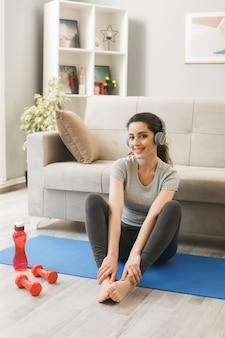 Glimlachend jong meisje met koptelefoon die traint op yogamat voor de bank in de woonkamer