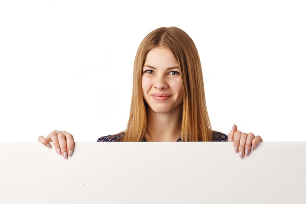 Glimlachend jong meisje met leeg wit bord over wit.