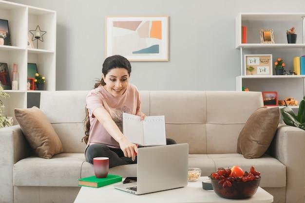 Glimlachend jong meisje met notitieboekje zittend op de bank achter de salontafel kijkend en wijst naar laptop in de woonkamer