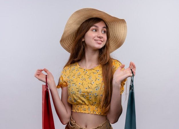 Glimlachend jong meisje met papieren zakken kijken rechts op geïsoleerde witte muur