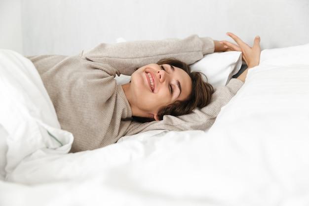 Glimlachend jong meisje ontspannen in bed in de ochtend, handen uitrekken