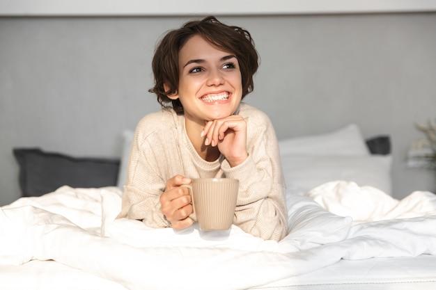Glimlachend jong meisje ontspannen in bed in de ochtend, koffiemok te houden