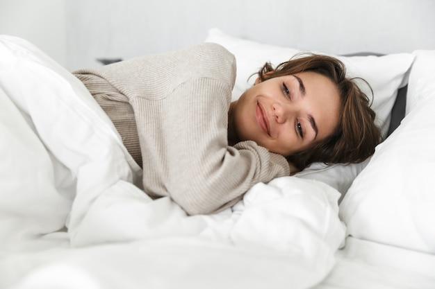Glimlachend jong meisje ontspannen in bed in de ochtend