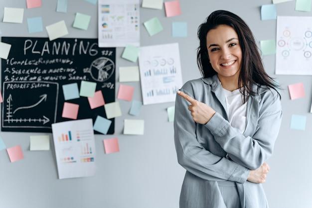Glimlachend jong meisje op kantoor wijst naar iets met haar wijsvinger