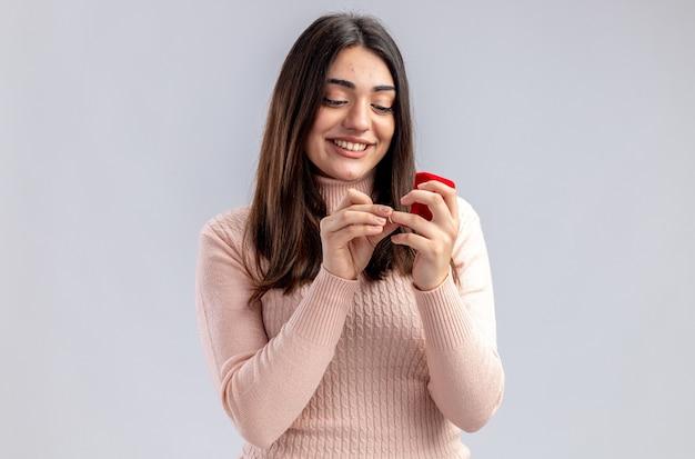 Glimlachend jong meisje op valentijnsdag houden en kijken naar trouwring geïsoleerd op een witte achtergrond
