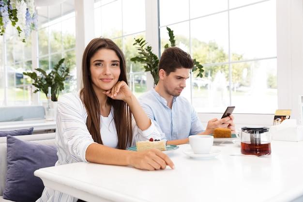 Glimlachend jong meisje, zittend aan de café tafel terwijl haar vriendje met behulp van mobiele telefoon