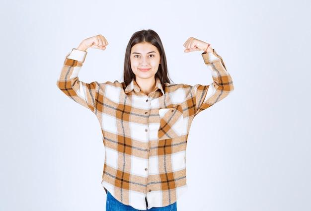 Glimlachend jong meisjesmodel dat haar biceps toont.
