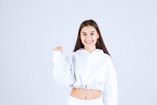 Glimlachend jong meisjesmodel dat zich en weg toont.