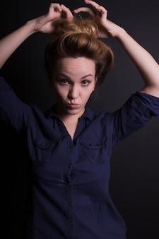 Glimlachend jong model in trendy kleding, poserend met grimas op een donkere studioachtergrond