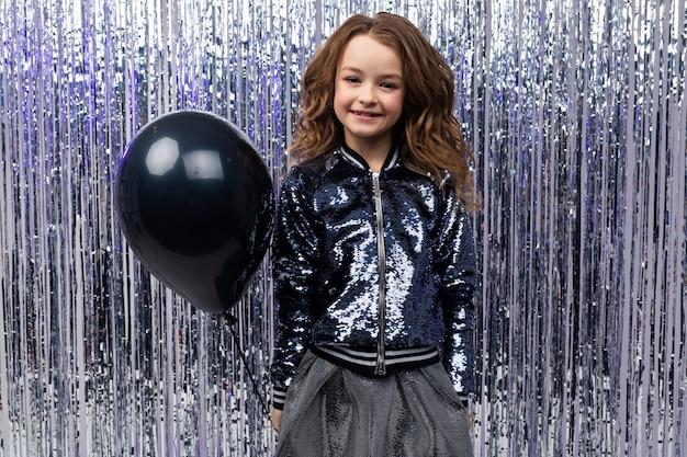 Glimlachend jong modieus kaukasisch meisje dat een zwarte ballon op een feestelijke muur houdt