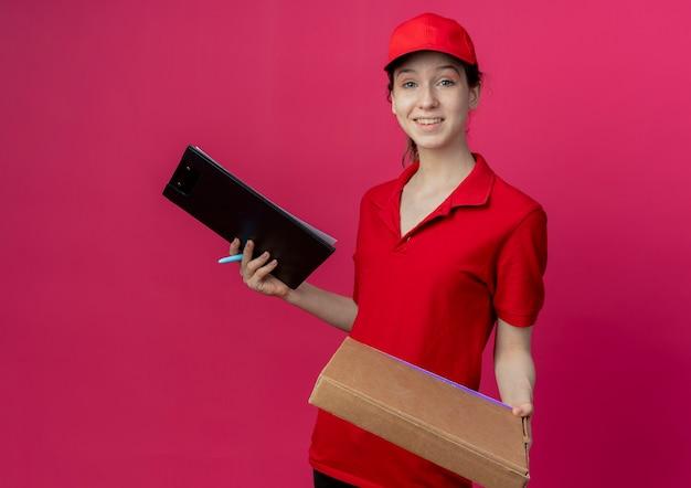 Glimlachend jong mooi bezorgmeisje in rood uniform en pet die pizzapakketpen en klembord houden die op karmozijnrode achtergrond met exemplaarruimte wordt geïsoleerd