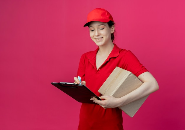 Glimlachend jong, mooi bezorgmeisje in rood uniform en pet met klembord en pen die met pen op klembord schrijft